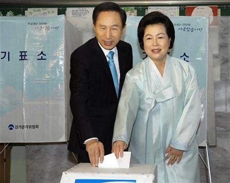 12月19日,大国家党总统候选人李明博和他的夫人在首尔一处投票站投票。