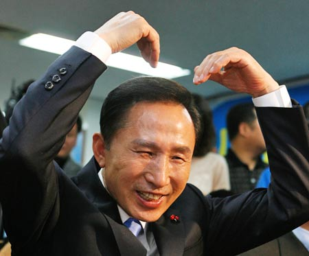 12月19日,李明博在首尔大国家党总部的电视会议上用手做出一个心形图案。