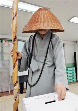 12月19日,一名韩国僧人在首尔一处投票站投票。