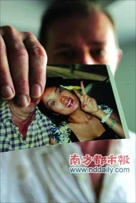 """米兰向记者展示他的""""中国女友""""阿娟的照片。"""