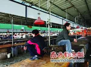 两名档主因不让其他人在他们档上摆卖猪肉,干脆坐到台上。