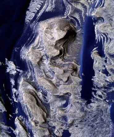 "NASA的""火星侦察轨道飞行器""拍摄到图片显示,液态水曾经流经火星表面层状岩石区的裂缝。"