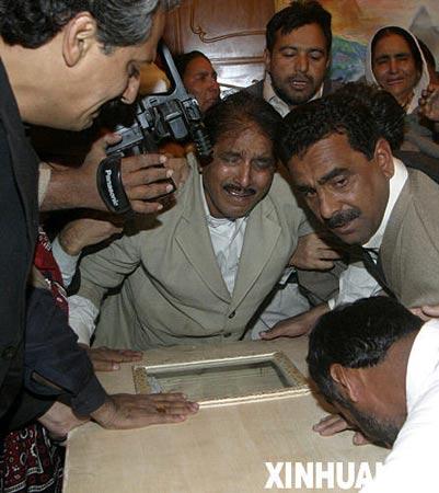 12月28日,在巴基斯坦南部信德省胡达巴赫什堡村举行的贝·布托的葬礼上,她的支持者抚棺哭泣。
