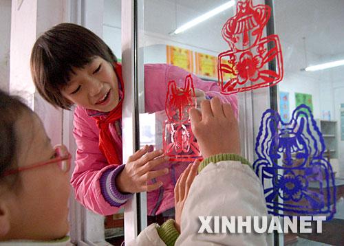 12月28日,安徽淮南市田家庵区洞山第二小学学生在教室玻璃窗上贴奥运题材的窗花。