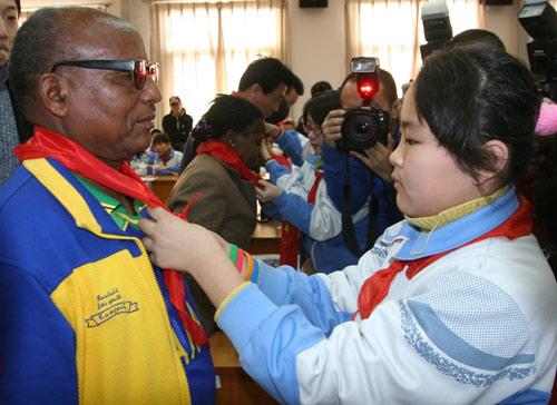 图文:阿赫瓦里与小学生共祝奥运 带上红领巾