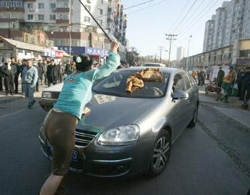 女子手持棍子试图爬到车前盖上-大连一女子持棍拦车 当街脱衣跳舞要钱图片