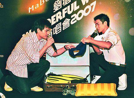 林家栋(左)代表公司送上泳裤、游泳用品给华仔,寓意终可放假休息