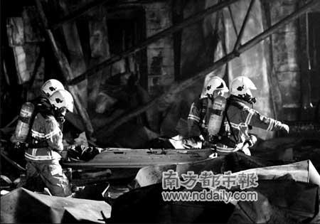 爆炸后的冷库废墟中,消防员运送烧得漆黑的死者尸体。