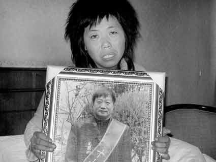 妻子曾静芳手中抱着丈夫魏文华的照片
