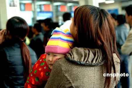 一名二岁的江西籍男童依偎在母亲的臂膀内,在福州火车站售票大厅排队等候购买春运返乡火车票。