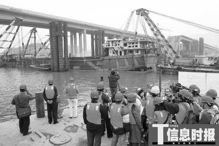 """昨日下午3时50分,九江大桥肇事船只""""南桂机035""""出水船体在4艘浮吊的牵引下驶离出事现场,拖离九江大桥400米左右的西江下游担担沙岛存放。时报记者"""