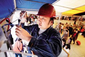 广铁集团照明段的何师傅正在火车站广场临时候车室进行照明安装。时报记者 黄立科 摄