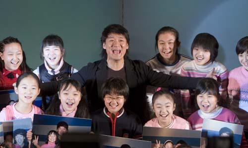 周华健高兴的与参与拍摄的孩子们合影