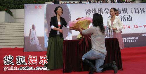 女歌迷单膝跪地献花