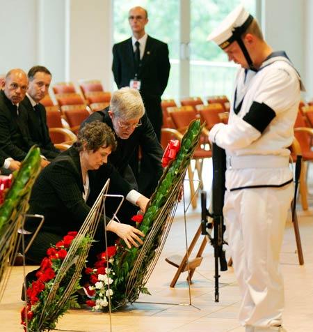 新西兰总理克拉克和她的丈夫向希拉里爵士的灵柩献花。