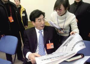 """昨天上午,北京市代市长郭金龙在参加平谷团审议的间隙翻看本报。审议中,有代表希望代市长以后能笑口常开。郭金龙看着自己在报纸上的照片笑着说,""""这张照片我就笑了""""。本报记者 张斌 摄"""