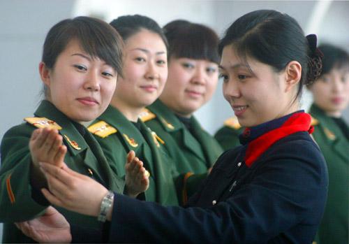 1月21日,沈阳边防检查站的出入境女检查员在礼仪培训员指导下进行手势培训。
