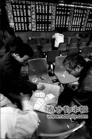 昨天,广州农林下路一个证券营业厅。几个股民聚在一起边玩牌边关注股市行情。本报记者方谦华摄