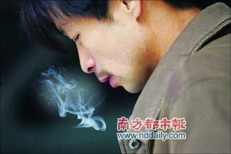 想到到了年底没钱回家,一民工心情沉重不停地抽烟。本报记者高贵彬摄