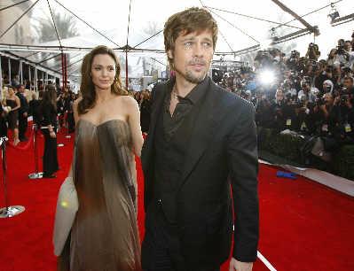 安吉莉娜·朱丽身着剪裁宽大的裙子在布拉德·皮特的陪伴下踏上红地毯,引发媒体猜测其再度怀孕