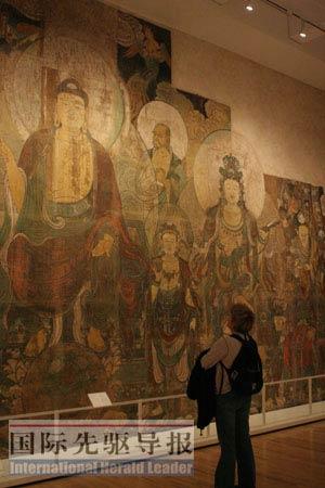 """一位游客在皇家安大略博物馆中国寺庙艺术展区观赏壁画""""弥勒佛的乐园""""。 捷克佳/摄"""