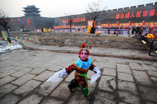 1月26日,在山西平遥古城,一个孩子赶往社火表演排练现场。