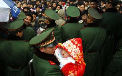 在铁路上海站值勤的武警战士,替一位旅客临时照顾婴儿。早报记者赵昀图