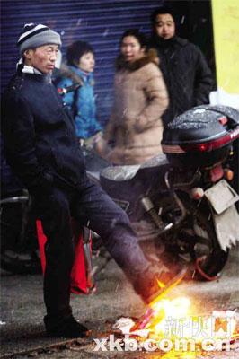 在汉口火车站,等火车的人生起火来取暖。