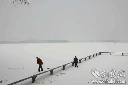 游人在东湖冰面上行走