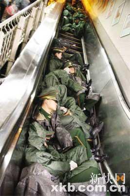 劳累至极的武警战士在地铁电梯上席地而卧和衣休息。 黄琼 陆建东/摄