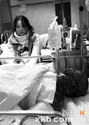 重伤的李满军正在救治中,女友一直守候在旁。