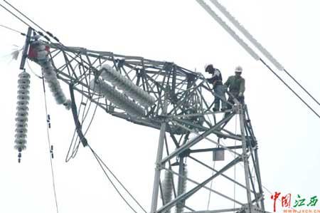 1月31日,协助萍乡市抗灾的省水电工程局的施工人员在白源街大陂村抢修塔头扭曲的220千伏安跑2号线线塔。安跑2号线是萍乡变电枢纽跑马坪变电站连接江西省500千伏主网的主要线路,直接影响到全市供电。记者在现场看到,维修工人沿着结冰的电线塔爬上塔头,修复扭曲的塔头。(唐念东/摄)