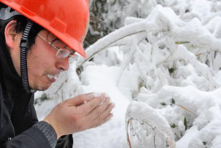 2月2日,一名电力抢险队队员在湖北省通山县抢险现场吃雪解渴。