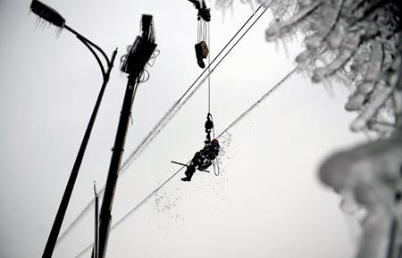 2月2日,一名电力工程人员在湖南?#24674;?#29579;仙岭用木棒清除电线上的积冰。