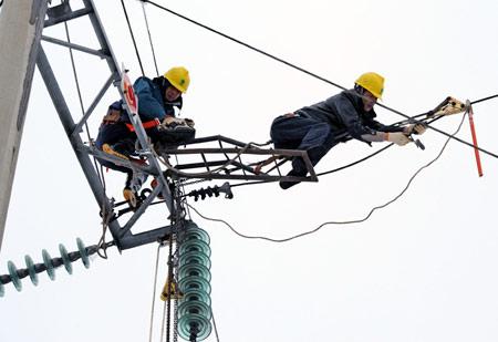 2月2日,衡阳电力局技术人员在海拔近千米的塔高山架上抢修输电线路。