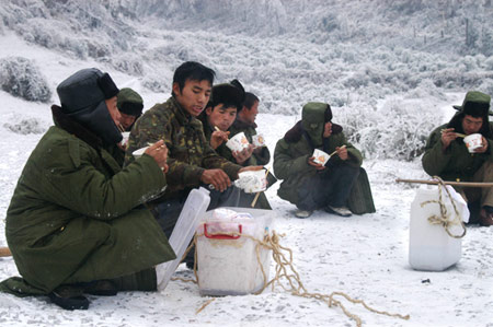 1月31日,贵州抢修一线的电力职工在冰雪中用餐。