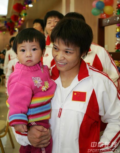 图文:体育健儿奥体中心捐款 冼冬妹抱着女儿