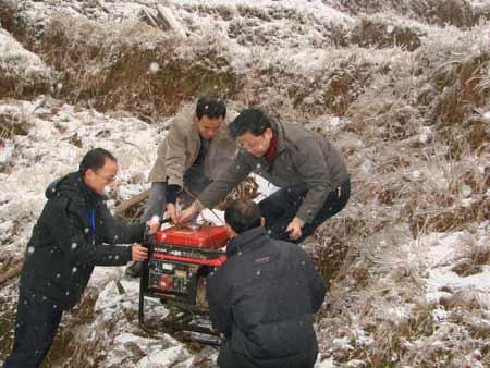 中国移动人员推拉并用将发电油机抬上基站