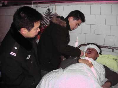 社区干部曾微和通泰街派出所所长唐江正在医院照顾熊双武。   卜劲文 摄