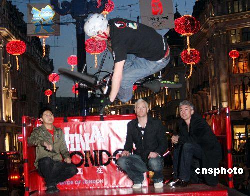 """当地时间6日晚,田亮和两名英国前世界冠军——三级跳远选手乔纳森·爱德华兹和四百米运动员伊万·托马斯共同在伦敦市中心启动了高悬在牛津街上的大红灯笼,""""中国在伦敦二00八""""系列中国新年庆祝就此开幕,图为田亮(左一)、爱德华兹(右一)和托马斯(中)在观看小轮车选手的高空特技表演。 中新社发 李鹏 摄"""