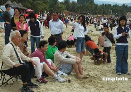 图为三亚大东海景区沙滩上休闲的游客。