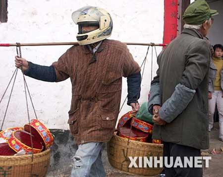 2月8日,一名村民戴着头盔挑着鞭炮从村中走过。 新华社发(刘念海 摄)