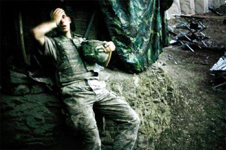 一名美国驻阿士兵斜靠在位于阿富汗一座山谷中的掩体内休息。这名士兵左手抱着钢盔,右手捂着额头和右眼,面部表情透着疲惫、焦虑和恐惧。画面色调灰暗。