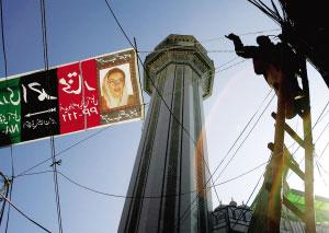12日,在古杰拉特街头,工人在悬挂巨幅选举广告横幅。新华社/法新