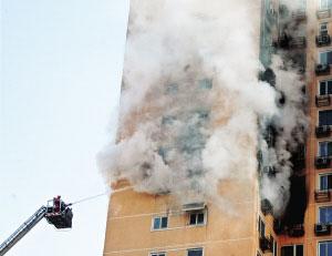 事发居民楼中冒出滚滚浓烟。本报实习生 王磊 摄