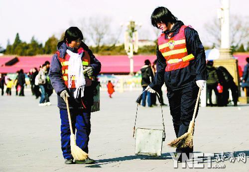 大学生清洁工(右)在广场工作很认真