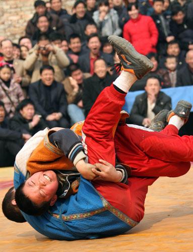 2月16日,两名摔跤手在?#28909;?#20013;。