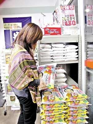 在日本,普通市民一般只买价格相对较低的大米。图为东京一家超市内,市民在选购大米。