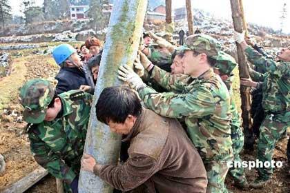 2月14日,贵州预备师高炮部队子弟兵在贵阳乌当区百宜乡场上村修复因雪灾损坏的电线杆,帮助当地受灾农户重建家园、恢复生产。 中新社发 pengnian 摄