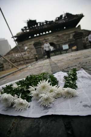 在崇礼门废墟前,市民放上白菊花以示哀悼。